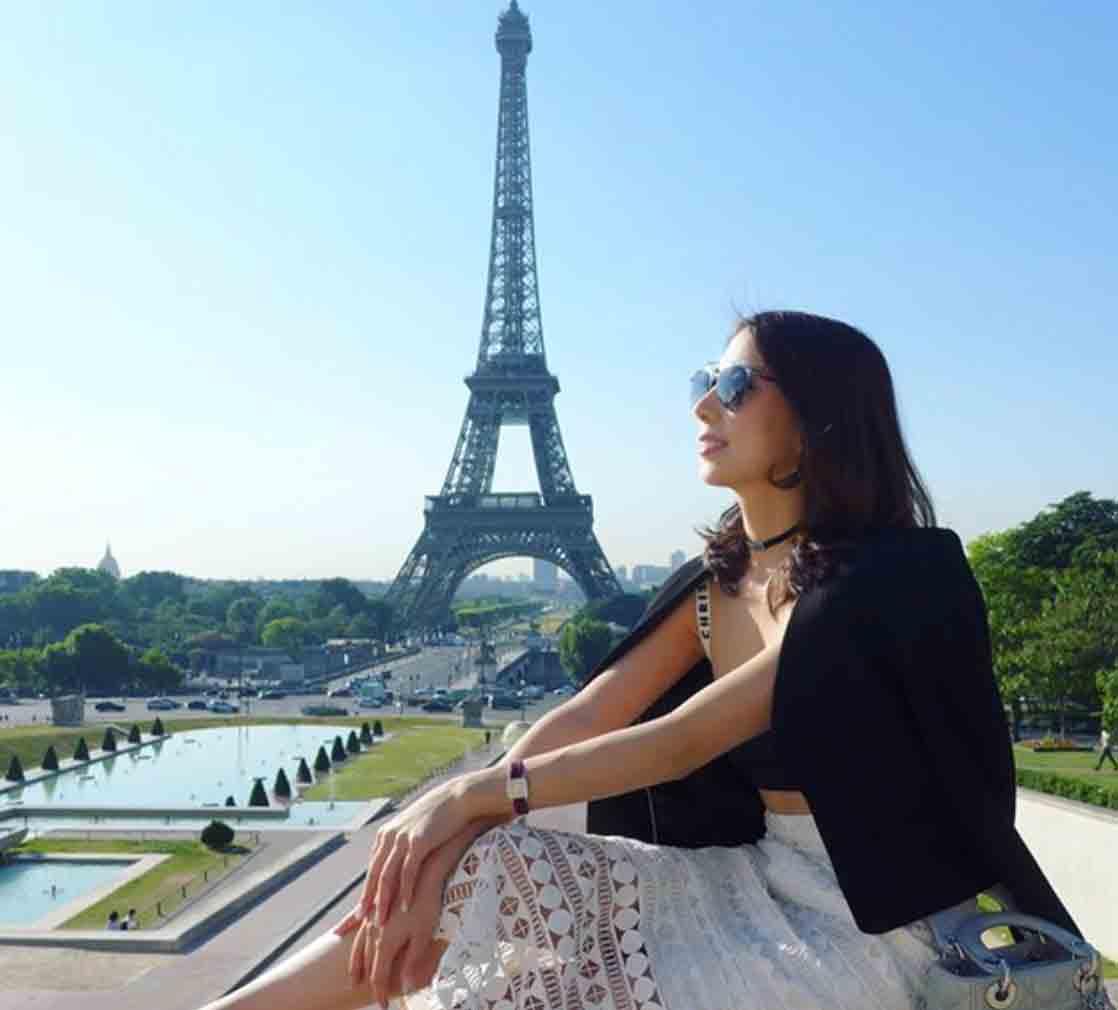 Dame på terrasse ved Eiffeltårnet